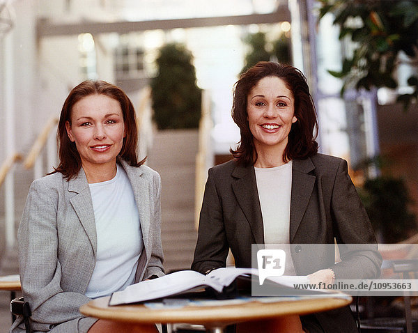 Portrait of two business women at a table.