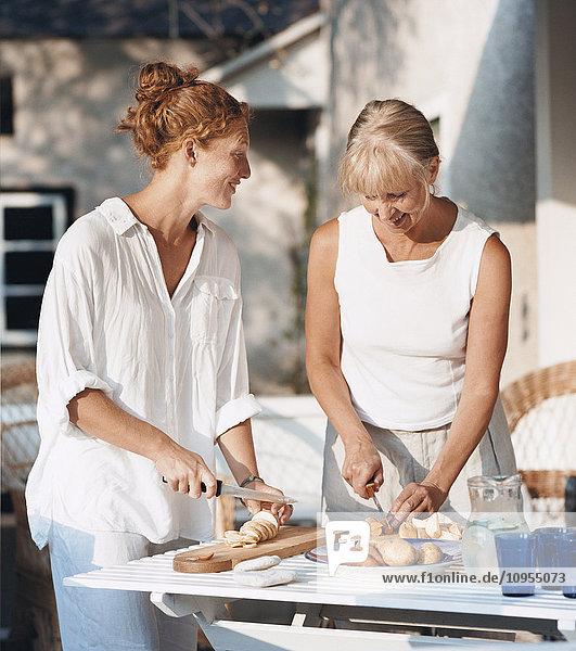 Smiling women preparing food outside