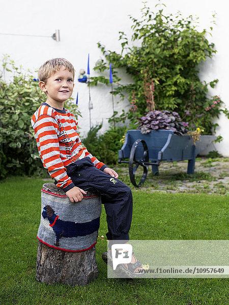 Boy sitting on a stump  Sweden.