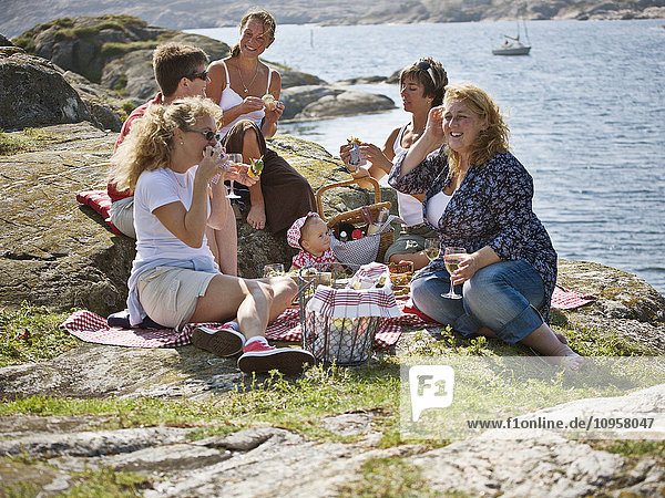 People having a picnic by the sea  Sweden.