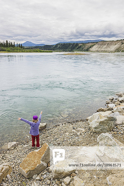 Young girl playing along the bank of the Yukon River  Whitehorse  Yukon Territory  Canada  Summer