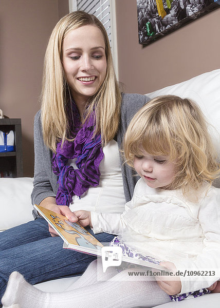 'Young disabled mother reading to her toddler daughter on a couch; Spruce Grove  Alberta  Canada'