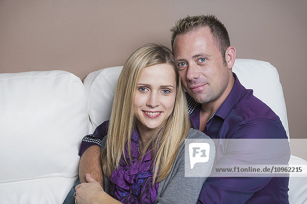 'Married couple cuddling on the couch  wife has a spinal cord injury and is a paraplegic; Spruce Grove  Alberta  Canada'