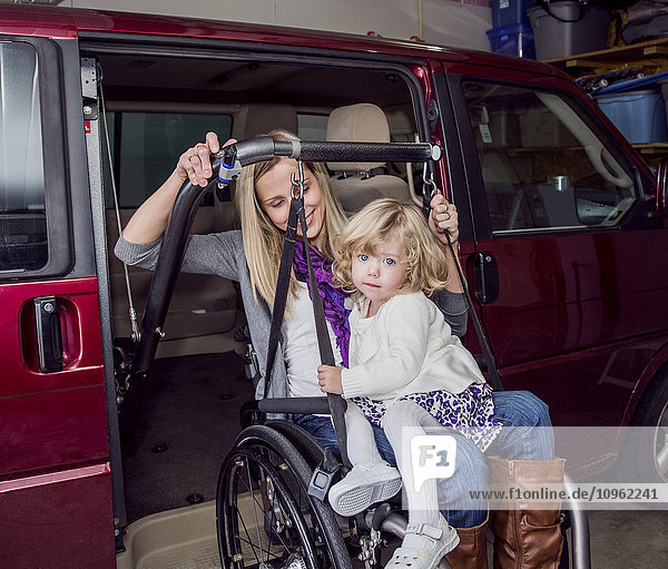 'Young disabled mother with her daughter using wheelchair powered device to assist with mobility to drive her vehicle; Spruce Grove  Alberta  Canada'