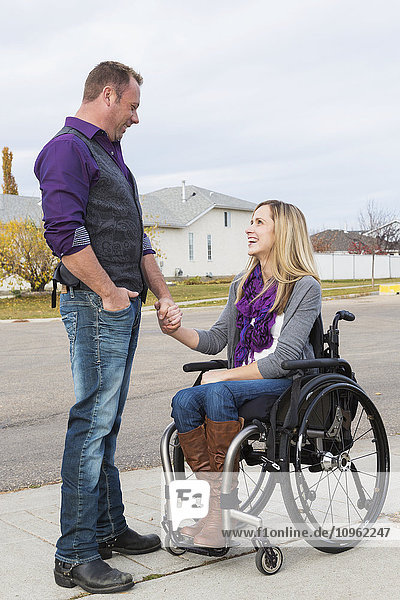 'Husband and wife with disability spending time together outdoors; Spruce Grove  Alberta  Canada'