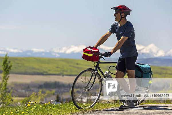 'Male cyclist standing with bike and bike bags on trail overlooking valley and snow capped mountains in the background with blue sky; Calgary  Alberta  Canada'
