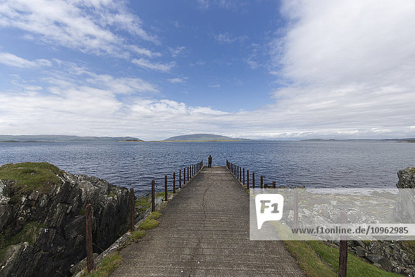 'Person standing at the end of a path at the water's edge looking out at the water; Argyll and Bute  Scotland'