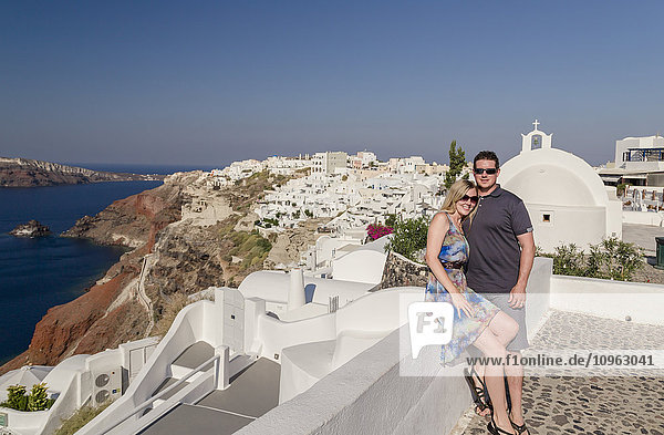 'A couple posing together on a white wall on a greek island with the town in the background; Santorini  Greece'