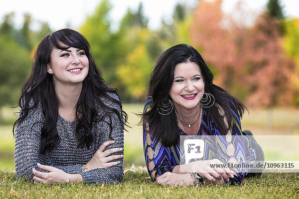 'Mother and daughter spending quality time together in a city park in autumn; St. Albert  Alberta  Canada'