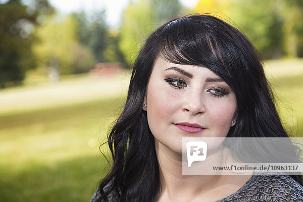 'Portrait of a beautiful young woman outdoors in a park in autumn; St. Albert  Alberta  Canada'