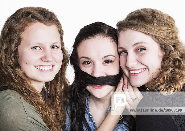 'Three young women in a humorous pose using long hair for a moustache; Alberta  Canada'
