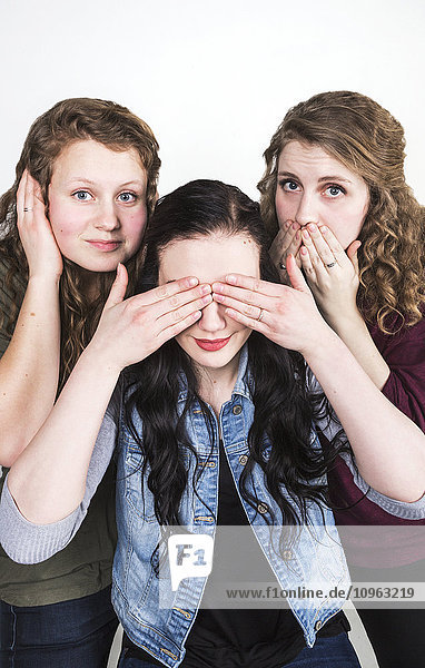 'Three young women doing humorous pose of Hear no evil  see no evil  speak no evil; Alberta  Canada'