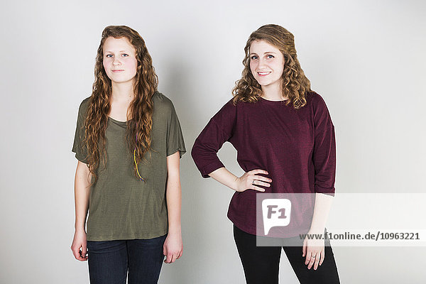 'Studio portrait of two young women against a white background; Alberta  Canada'