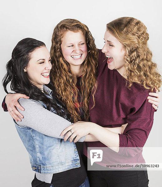 'Portrait of three young women hugging each other  on a white background; Alberta  Canada'