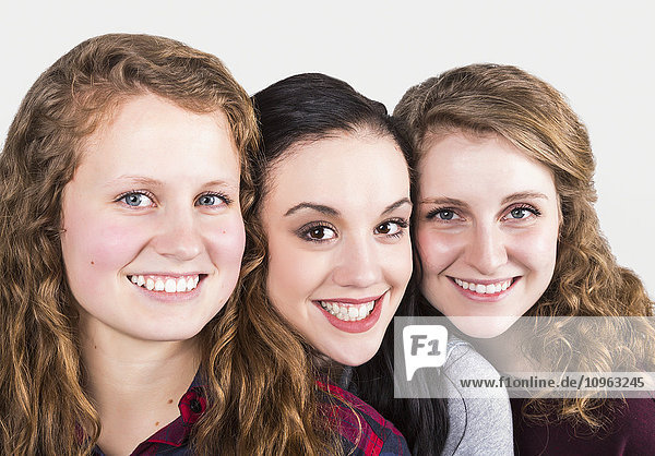 'Portrait of three young women on a white background; Alberta  Canada'
