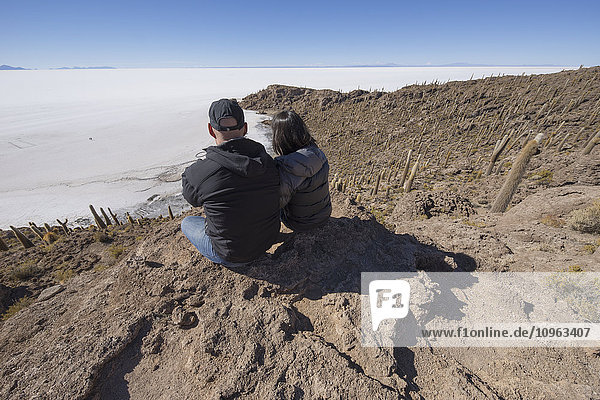 'Couple sitting on an island of rock and cactus called Incahuasi; Uyuni  Bolivia'