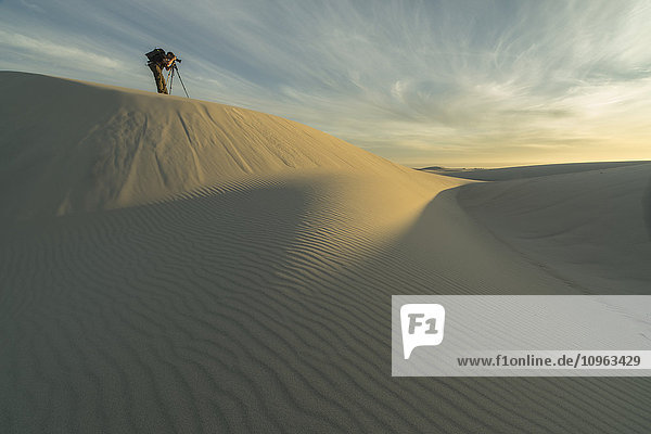 'Person taking photos in the white sand desert of Namakwaland National Park; South Africa'