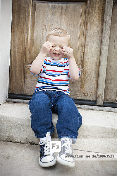 'A young boy sitting on a step and laughing; Nashville  Tennessee  United States of America'