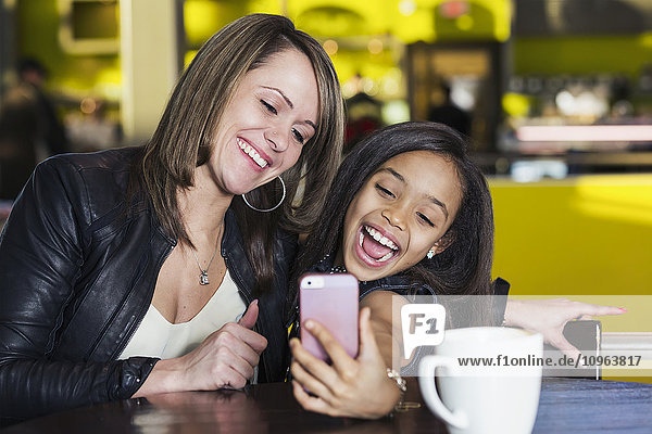 'Young mother and her daughter in a cafe looking at a smart phone and taking a selfie while taking a break from shopping; St. Albert  Alberta  Canada'