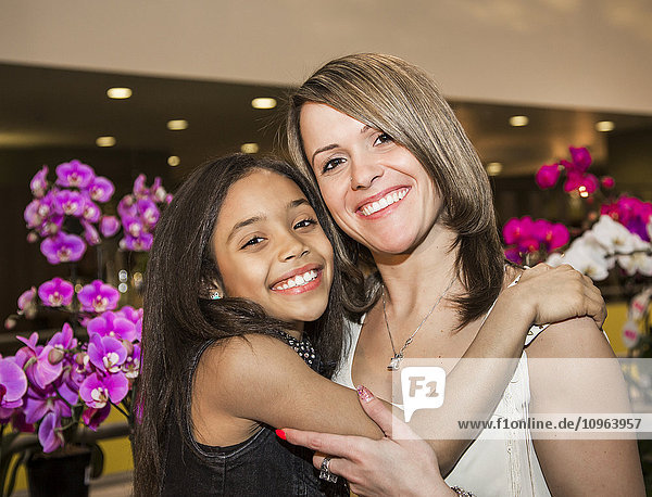 'Portrait of a young mother and her daughter posing in a mall in front of flowers; St. Albert  Alberta  Canada'