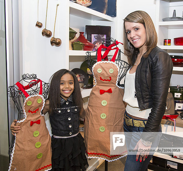 'Young mother and her daughter shopping at a kitchen store looking at aprons; St. Albert  Alberta  Canada'