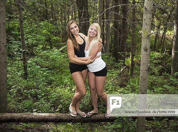 'Two teenage girlfriends hugging and balancing on a fallen log in the forest in a park; Edmonton  Alberta  Canada'