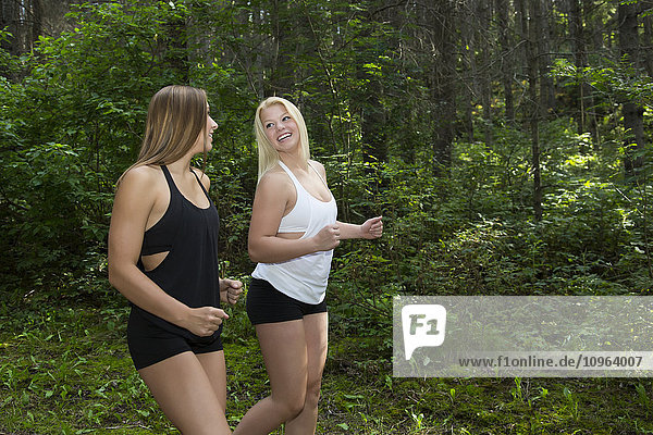 'Two young athletic girls jogging in the woods in a park; Edmonton  Alberta  Canada'