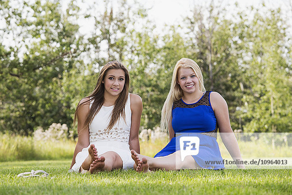 'Two girlfriends spending time together in a park in their dresses; Edmonton  Alberta  Canada'