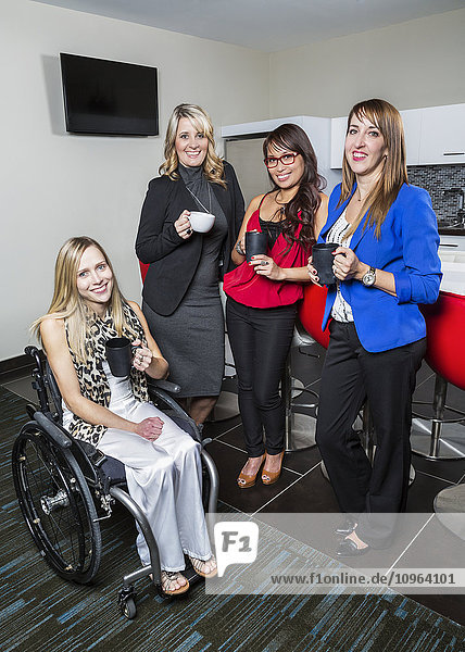 'Co-workers gather in kitchen with disabled peer for coffee break; St. Albert  Alberta  Canada'