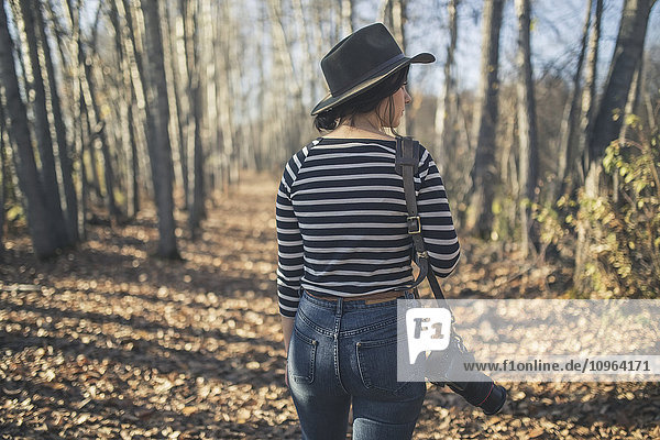 Young woman wearing hat with camera and walking through the woods near Creamer's Field  Fairbanks  Interior Alaska  Autumn