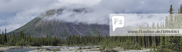 'Clouds cover the tops of the mountains along the Wind River in the Peel watershed; Yukon  Canada'