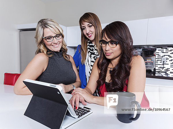 'Three professional business women looking on social media while taking a break in an office kitchen area; St. Albert  Alberta  Canada'