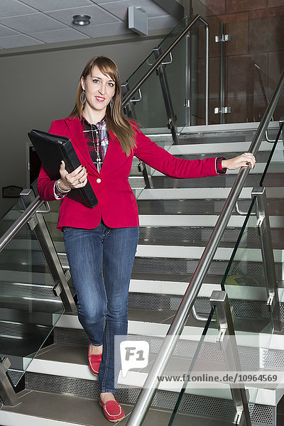 'Portrait of a young business woman on a stairway in an office; St. Albert  Alberta  Canada'