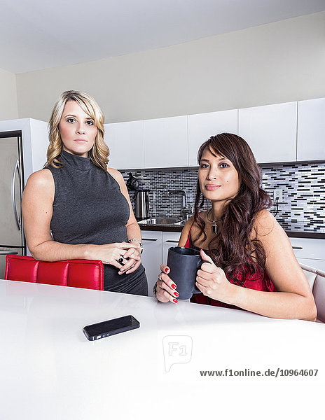 'Two professional business women taking a break in an office kitchen area; St. Albert  Alberta  Canada'