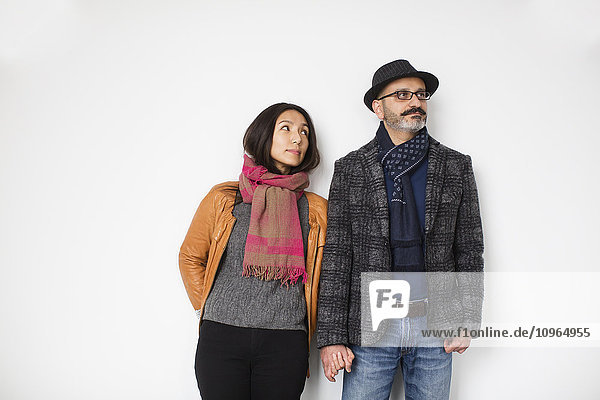 'Persian man and Tibetan woman holding hands and leaning against a wall  man looking away while woman is looking at man; Toronto  Ontario  Canada'