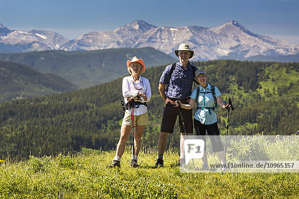 'Three hikers  two female and one male  on top of grassy hill with rolling foothills and mountain range in the background with blue sky; Kananaskis Country  Alberta  Canada'