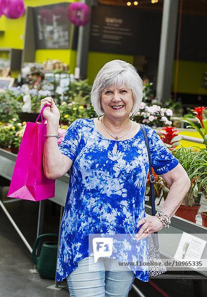 'Mature woman shopping in a garden centre in an indoor mall; St. Albert  Alberta  Canada'
