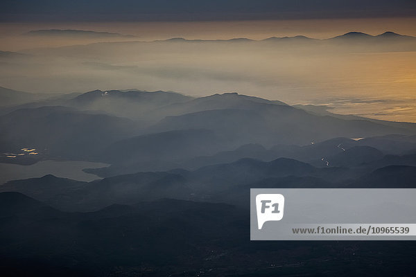 'View of mountains and clouds at sunset along the coastline; Greece'