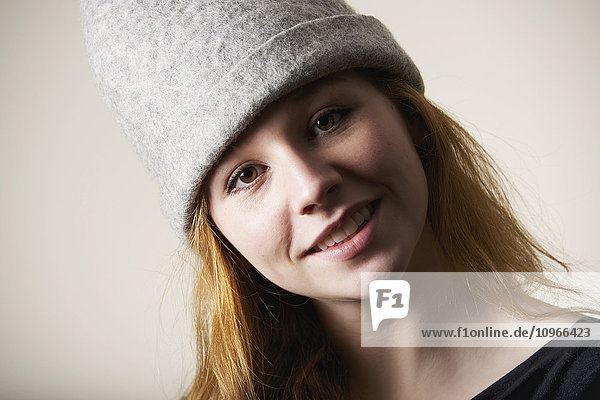 'Portrait of a smiling young woman with red hair and a grey hat; Caldecott  England'