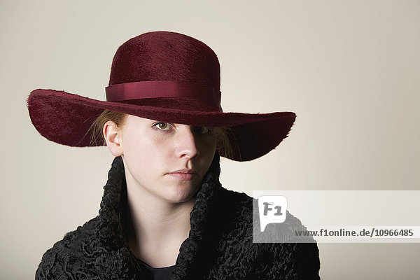 'Young woman with red hair in maroon hat and black coat; Caldecott  England'
