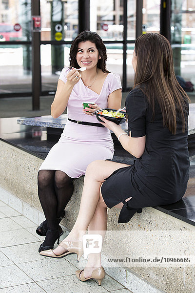 'Two business women having lunch together in the atrium of an office building; Edmonton  Alberta  Canada'