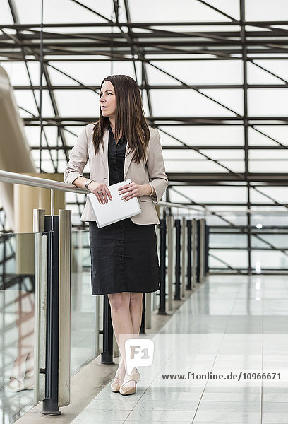 'Mature business woman standing in an atrium of an office building and holding a tablet; Edmonton  Alberta  Canada'
