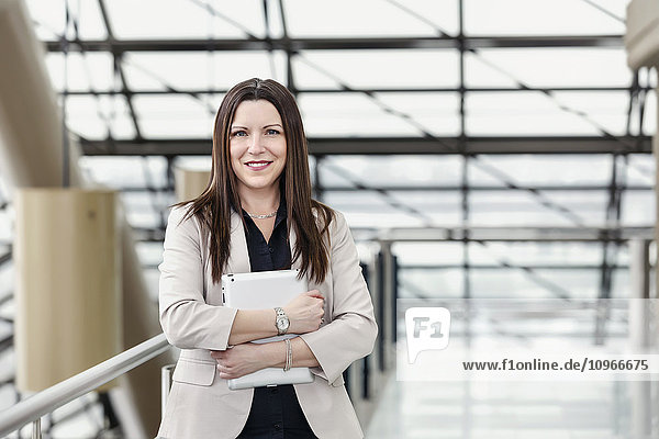 'Mature business woman posing in an atrium and holding a tablet; Edmonton  Alberta  Canada'