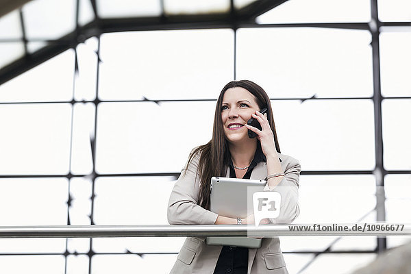 'Mature business woman talking on her smart phone and holding a tablet in the atrium of an office building; Edmonton  Alberta  Canada'