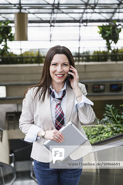'Business woman on an escalator talking on her cell phone and holding a tablet; Edmonton  Alberta  Canada'
