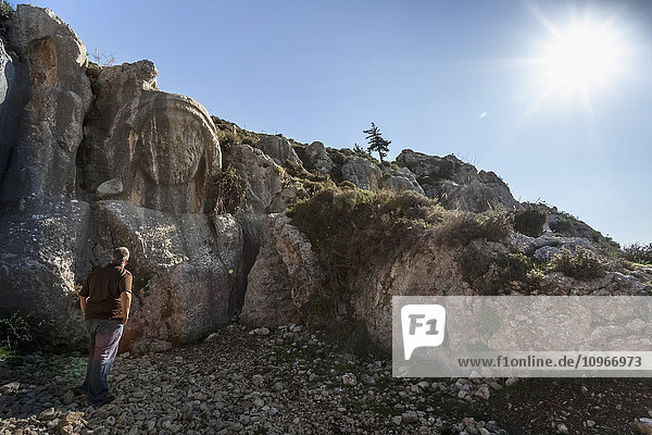 'A man stands looking at a carving in a rugged rock cliff; Antioch  Turkey'