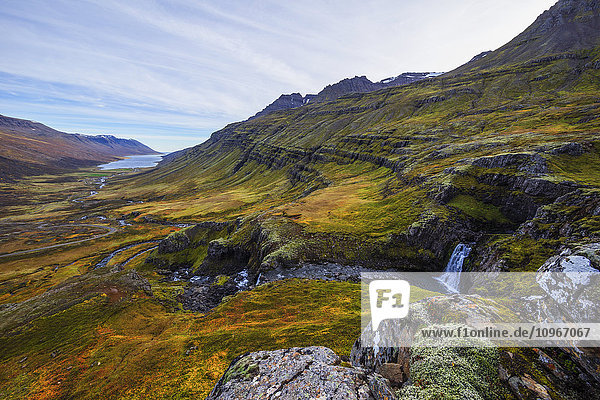 'A small waterfall on the rugged landscape of Mjoifjordur  East Fjords; Iceland'