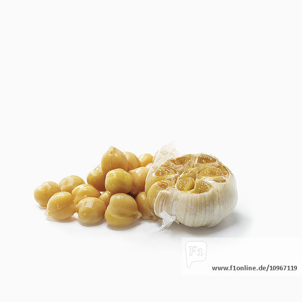 'Chick peas and cloves of garlic on a white background; Toronto  Ontario  Canada'