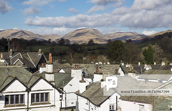 'White houses and rooftops with mountains in the distance; Hawkshead,  England'