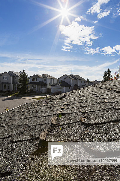 'Close up of well worn rounded roof shingles with neighbourhood houses  sun burst  blue sky and clouds in the background; Calgary  Alberta  Canada'